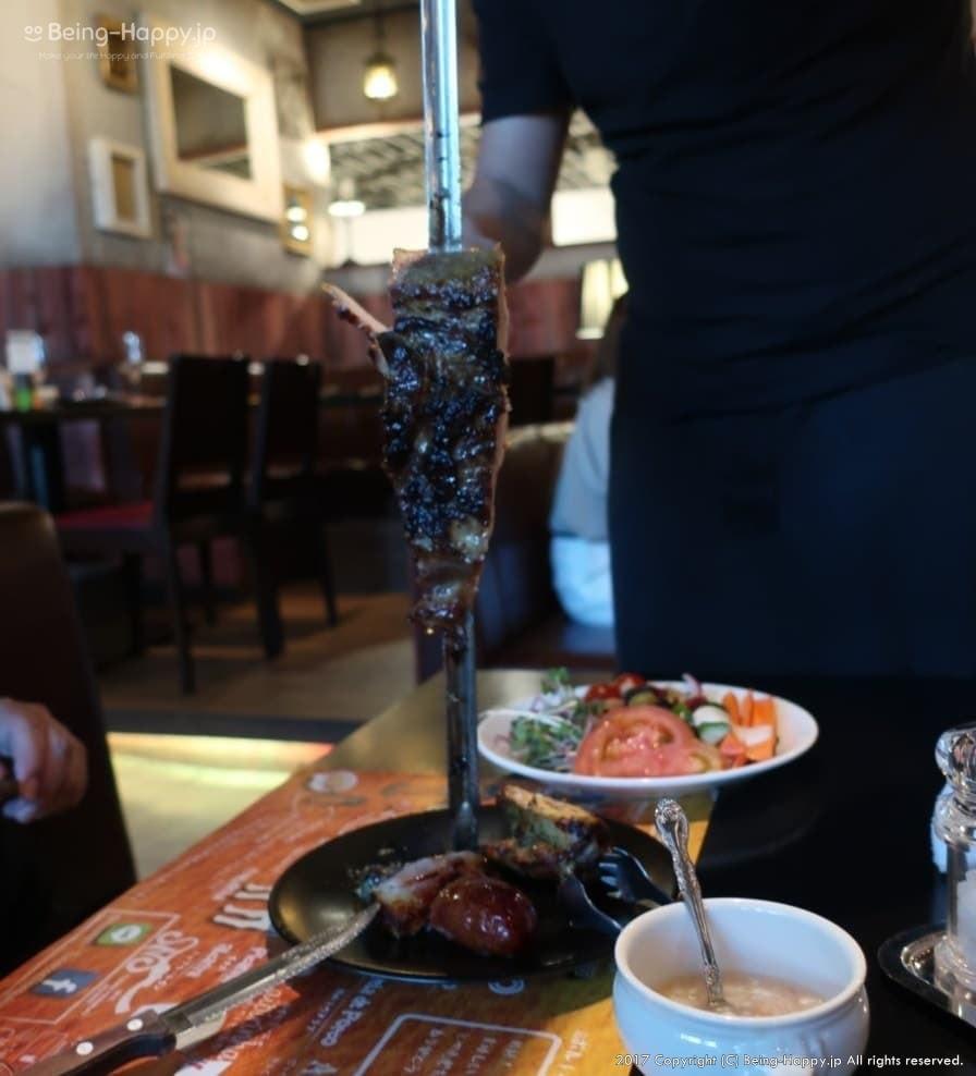 TUCANO'S(トゥッカーノ)池袋ー店員さんが肉の塊を持ってテーブルを回っている様子