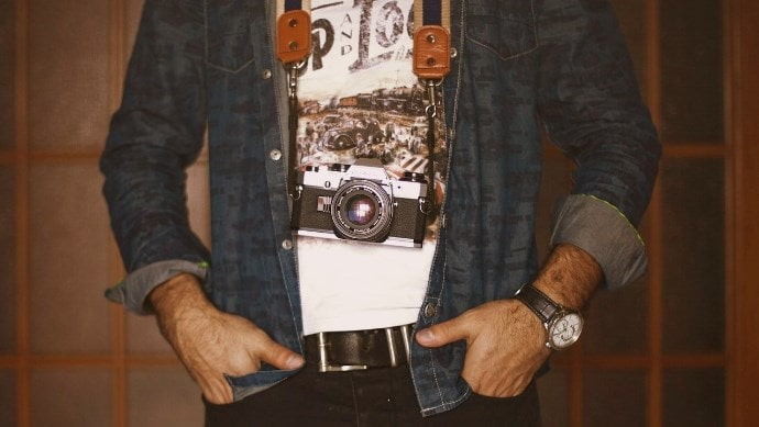 カメラを肩にかける男性